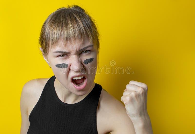 uma mulher com camuflagem no rosto em um fundo amarelo mostra um punho e grita um grito de guerra conceito de feminismo foto de stock