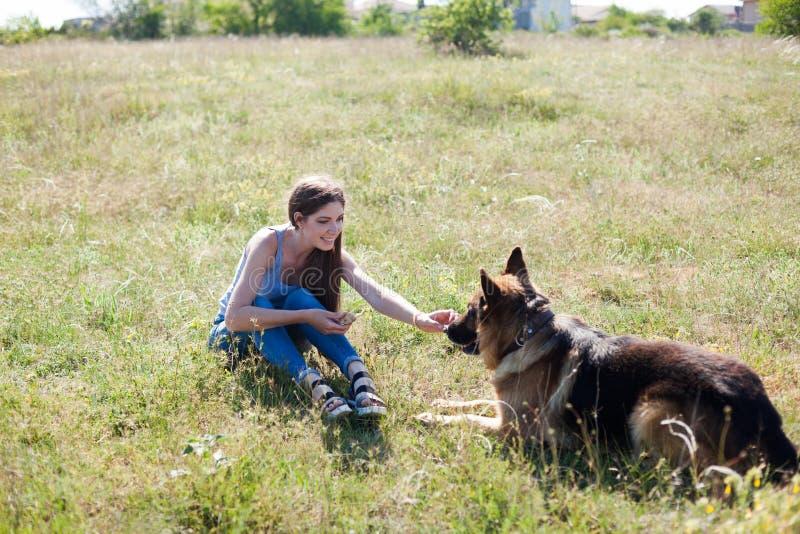 Uma mulher com uma criança com treinamento do pastor alemão fotografia de stock