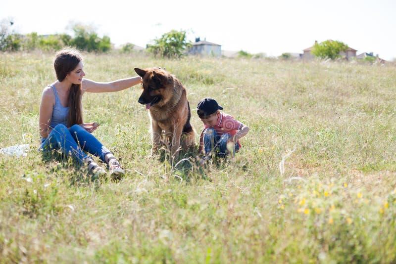 Uma mulher com uma criança com treinamento do pastor alemão imagens de stock royalty free