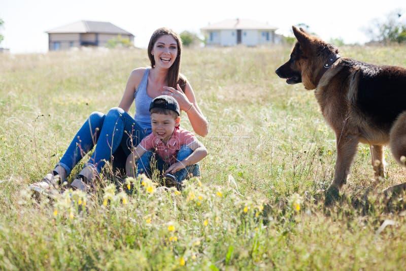 Uma mulher com uma criança com treinamento do pastor alemão imagem de stock royalty free