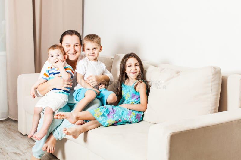 Uma mulher com crianças está sentando-se no sofá foto de stock royalty free