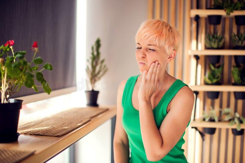 Uma mulher com dor em seus dentes está mantendo sua cara interna Povos, saúde e conceito médico foto de stock royalty free