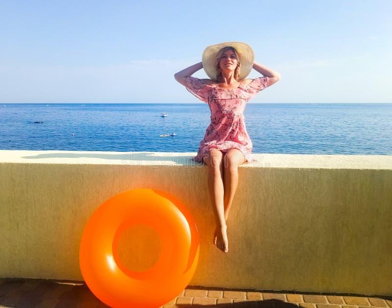 Uma mulher com uma figura bonita está sentando-se em uma cerca concreta na frente do mar Inflável alaranjado de Nogshinahschiny imagem de stock