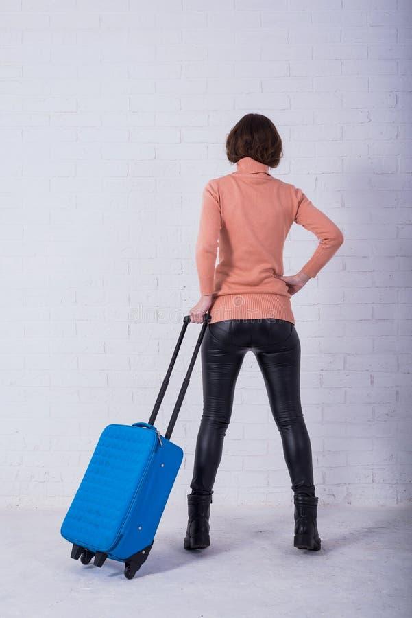 Uma mulher com uma mala de viagem azul perto de uma parede de tijolo branca, espa?o da c?pia imagem de stock