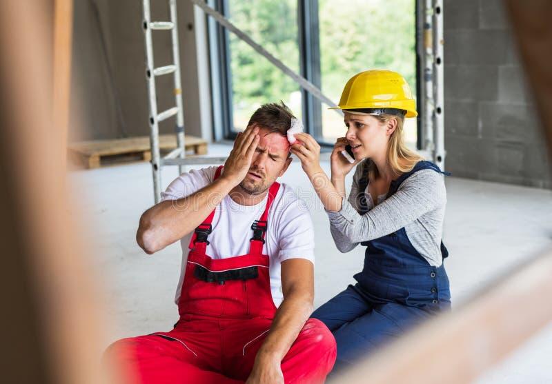 Uma mulher com o trabalhador de ajuda do homem do smartphone após um acidente no canteiro de obras fotos de stock royalty free
