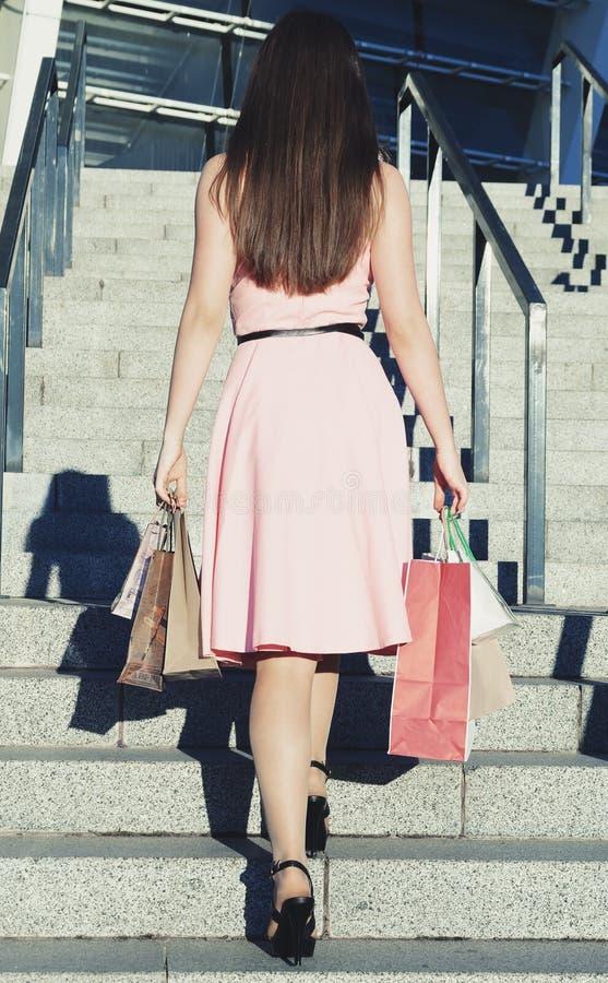Uma mulher com sacos de papel vai acima das escadas à construção fotografia de stock royalty free