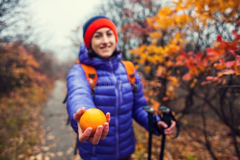 Uma mulher com uma trouxa dá uma laranja fotografia de stock