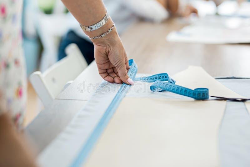 Uma mulher com um bracelete está medindo a tela Forma, a oficina do alfaiate fotografia de stock royalty free