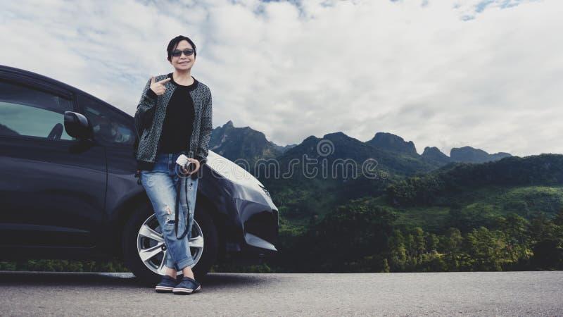 Uma mulher com um carro na estrada e na montanha no fundo fotografia de stock royalty free