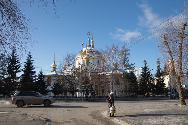 Uma mulher com um saco de compras anda no passeio após a catedral da ascensão - o templo principal da cidade de Novosibirsk dentr foto de stock