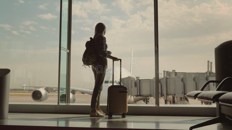 Uma mulher com um saco do curso e passagens de embarque em sua mão olha um avião de passageiros enorme atrás do terminal de aerop imagens de stock royalty free