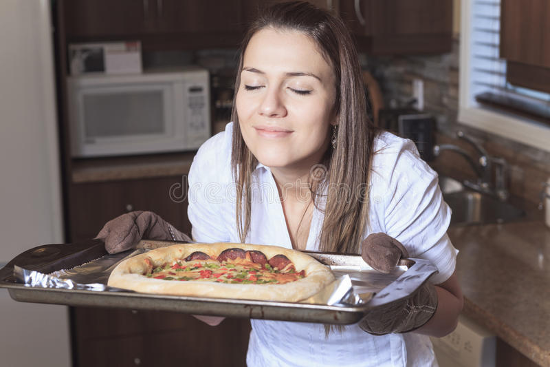 Uma mulher com uma pizza deliciosa na cozinha foto de stock