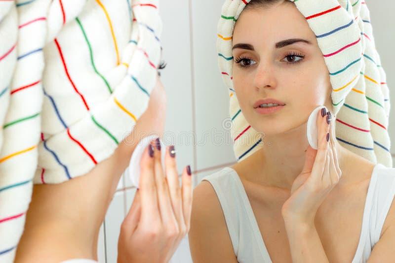 Uma mulher com uma toalha em sua cabeça cancela a reforma facial fotografia de stock royalty free