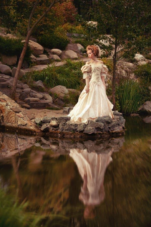 Uma mulher como uma princesa em um vestido do vintage imagem de stock royalty free