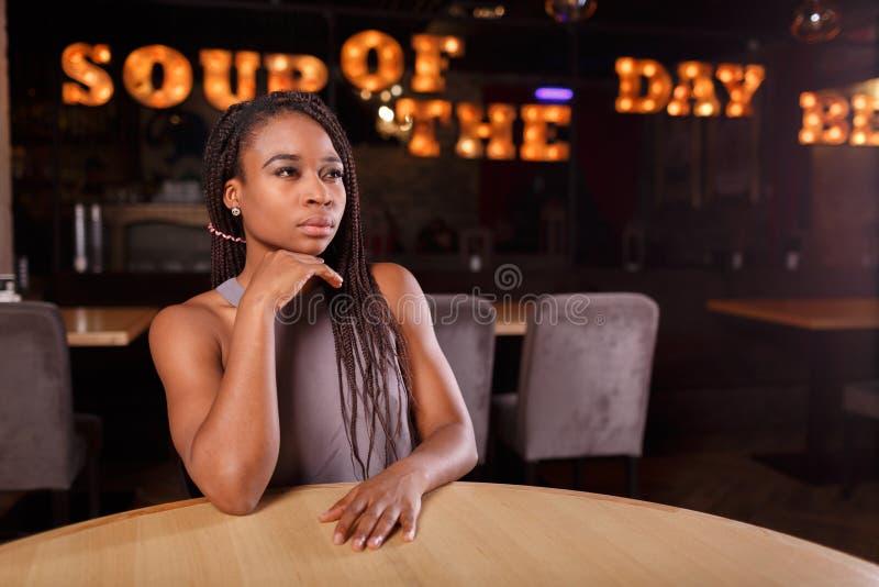 Uma mulher consideravelmente afro-americana em um café foto de stock