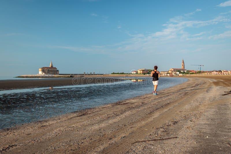 Uma mulher corre à praia foto de stock royalty free