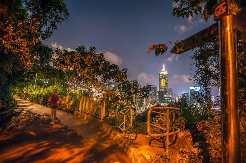 Uma mulher corre ao longo da fuga na noite, Wan Ch da aptidão da estrada de Bowen foto de stock