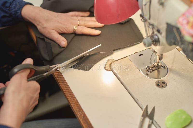 Uma mulher corta o material antes de processar na máquina de costura fotos de stock royalty free