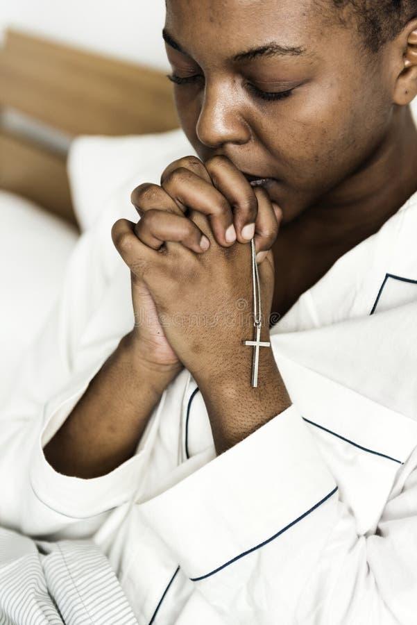 Uma mulher cristã que reza na cama fotografia de stock royalty free