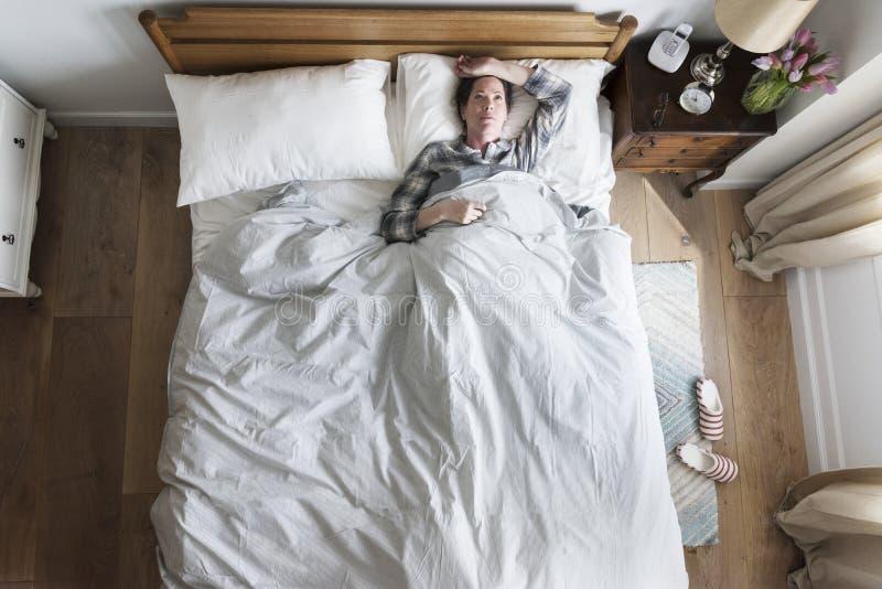 Uma mulher da insônia na cama imagens de stock royalty free