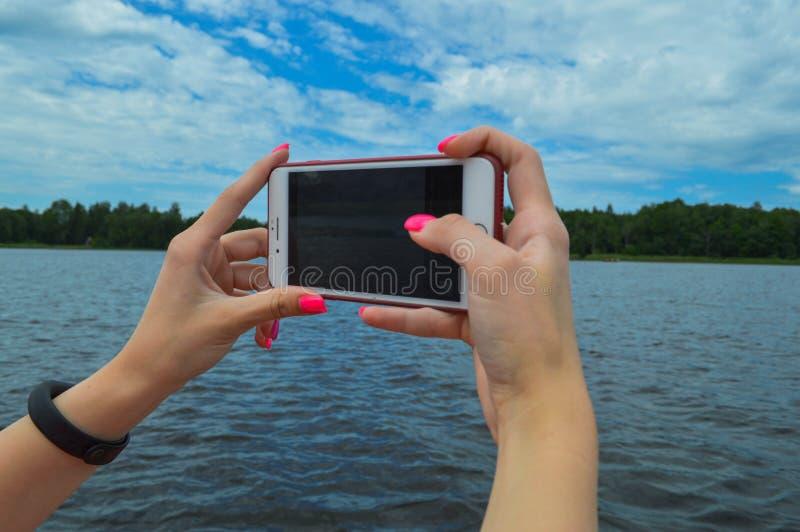 Uma mulher da menina com realizar alaranjados cor-de-rosa do tratamento de mãos bonito dos pregos em suas mãos um smartphone do t foto de stock royalty free