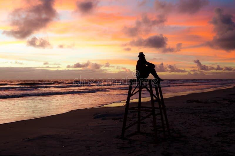 Uma mulher da silhueta que senta-se em uma torre da salva-vidas que aprecia o nascer do sol em uma praia e no ` s do sol irradia  fotos de stock royalty free