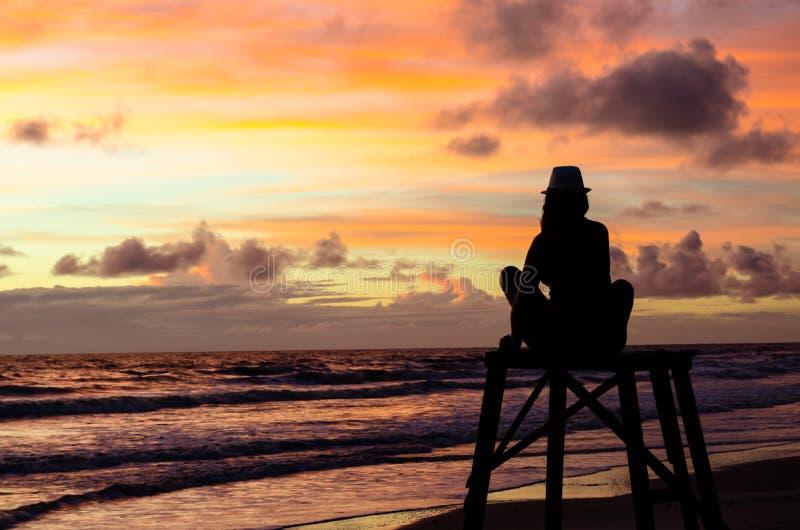 Uma mulher da silhueta que senta-se em uma torre da salva-vidas que aprecia o nascer do sol em uma praia e no ` s do sol irradia  fotos de stock