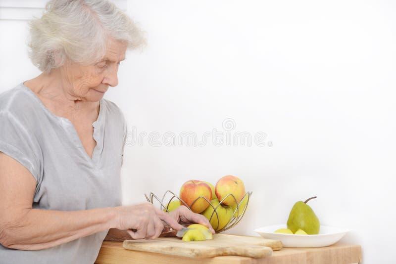 Uma mulher das pessoas de 80 anos que corta maçãs na cozinha imagem de stock