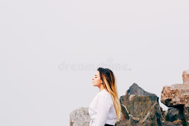 Uma mulher de cabelos compridos consideravelmente nova na camisa branca em uma praia fotos de stock royalty free