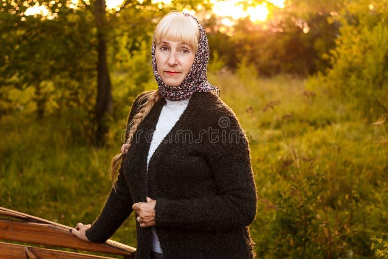 Uma mulher de cinquenta anos bem arrumado com uma trança olha a câmera no verão no por do sol fotos de stock