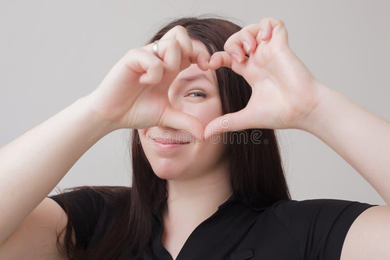 Uma mulher de meia idade bonita em um t-shirt preto guarda suas mãos perto do facein o formulário de um coração imagens de stock royalty free