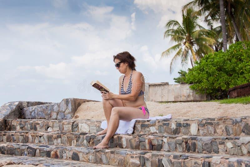 Uma mulher de meia idade que lê um livro foto de stock