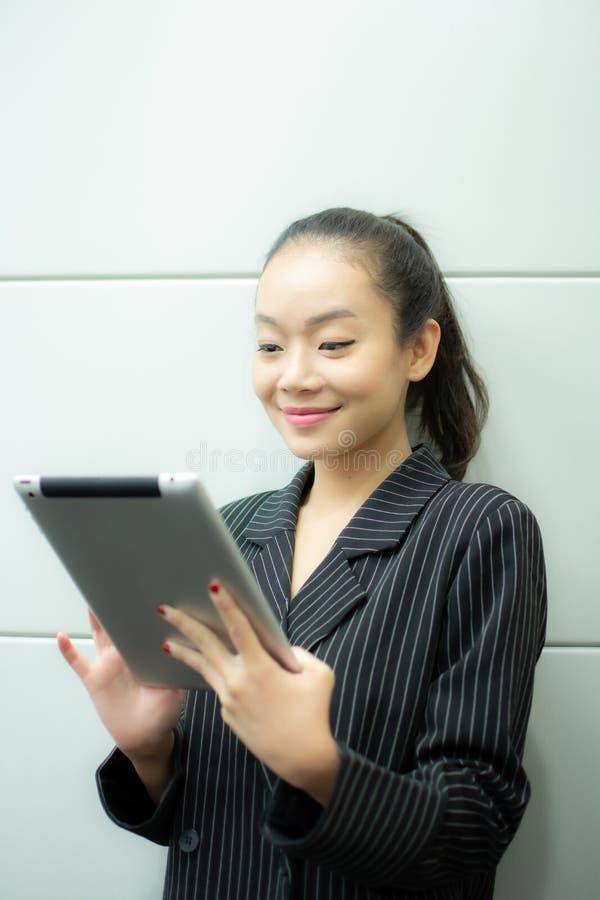 Uma mulher de negócio asiática está usando a tabuleta foto de stock