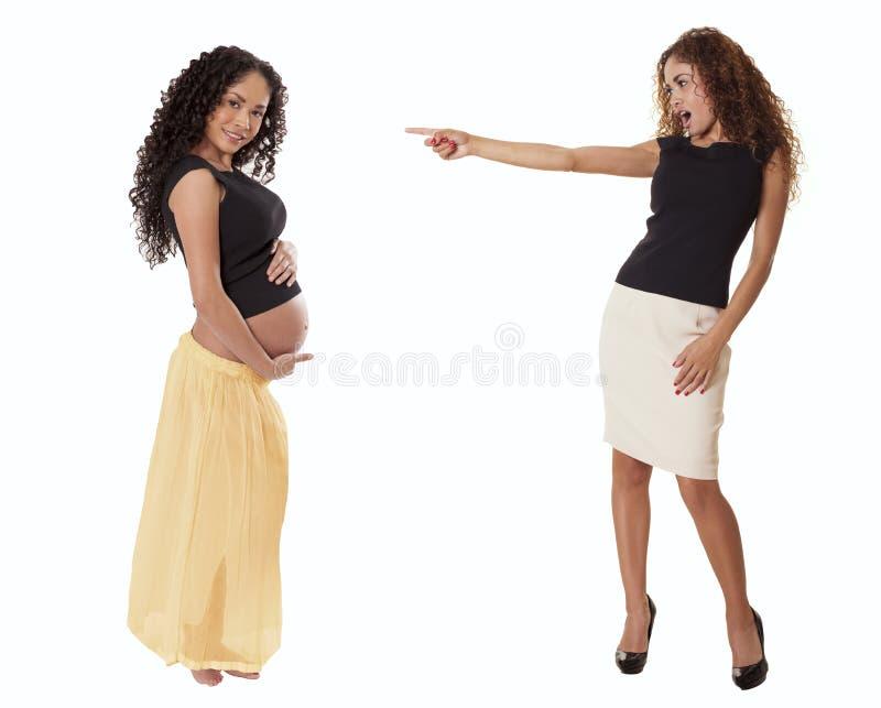 Uma mulher de negócio do ajuste em uma saia aponta com choque em um grávido imagens de stock