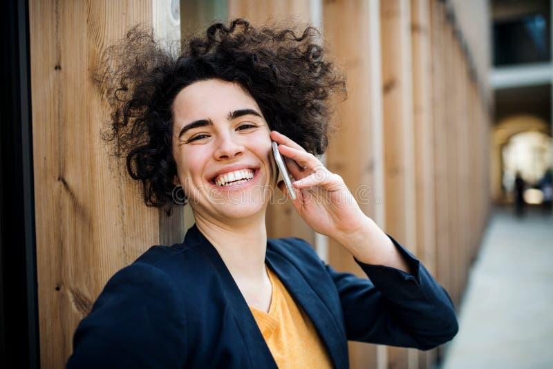 Uma mulher de negócio nova feliz com o smartphone que está fora fotografia de stock royalty free