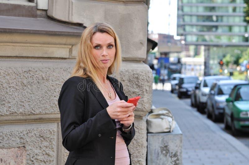 Uma mulher de negócio nova feliz que usa um telefone esperto fora