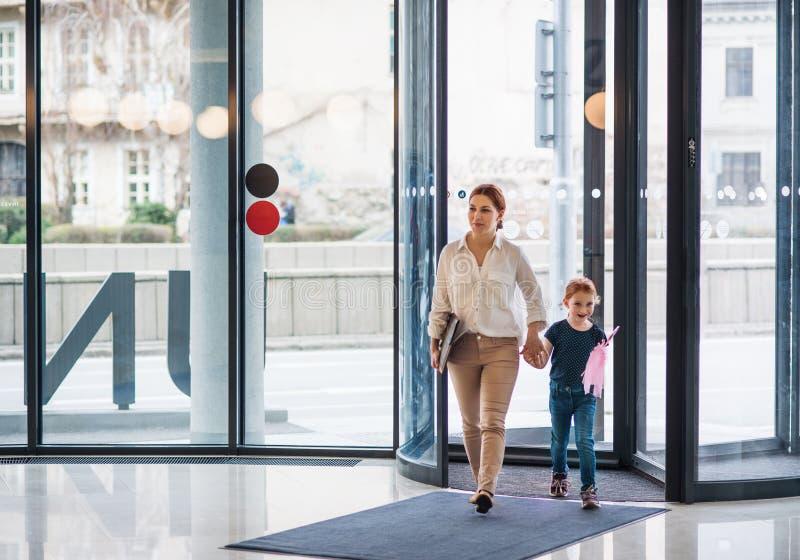 Uma mulher de negócios com o prédio de escritórios entrando da filha pequena, andando imagem de stock royalty free
