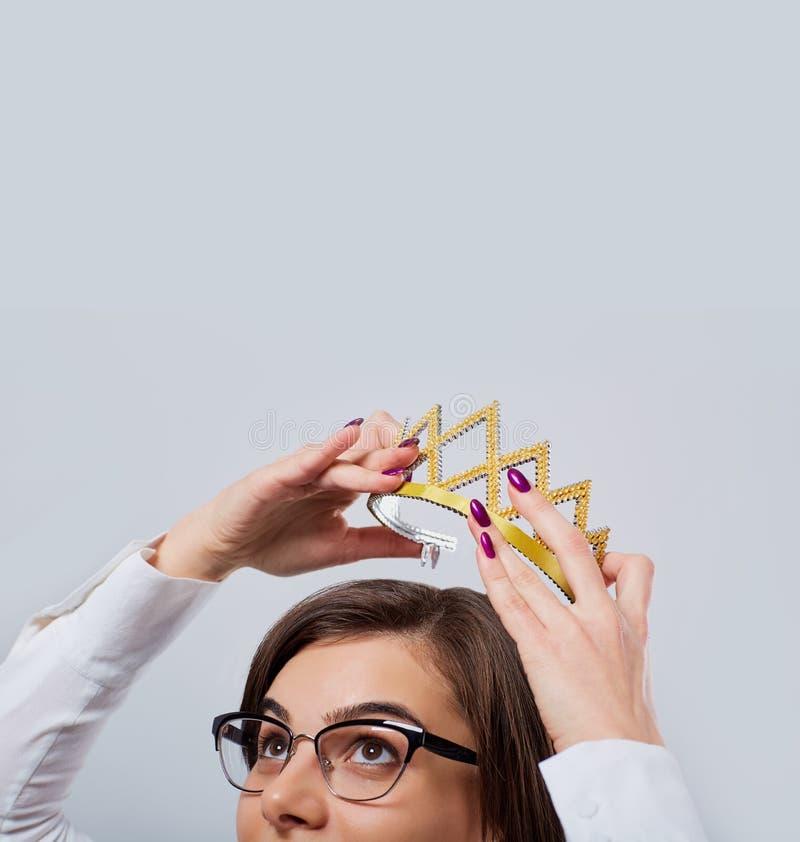 Uma mulher de negócios está guardando uma coroa sobre sua cabeça imagens de stock