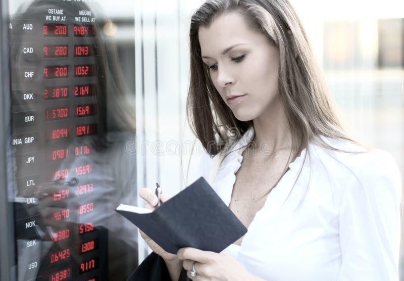 Uma mulher de negócios nova está verific a moeda fotos de stock