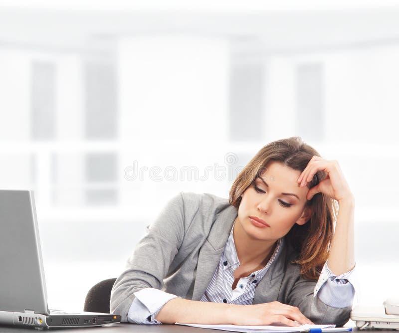 Uma mulher de negócios nova que sente cansado no trabalho fotografia de stock royalty free