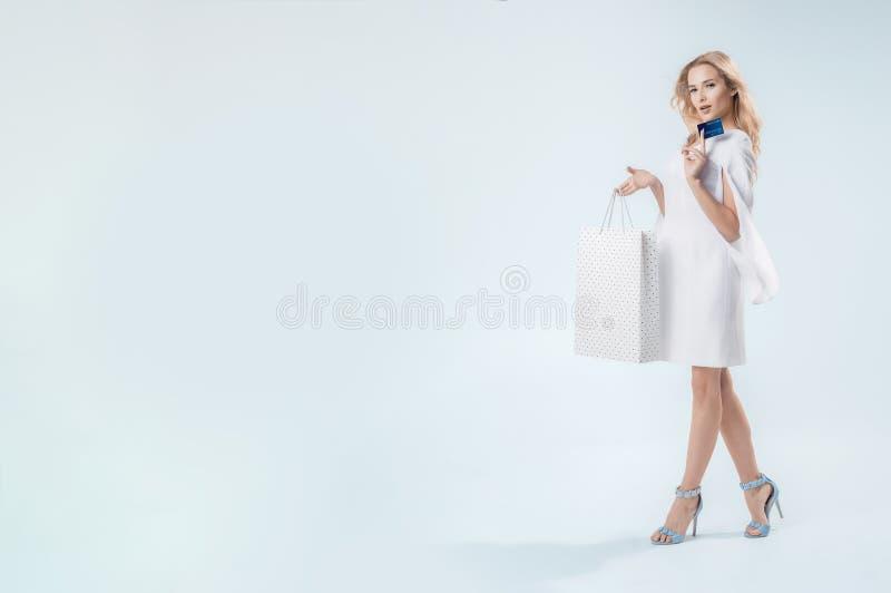 Uma mulher de sorriso elegante está com um cartão de crédito imagens de stock royalty free