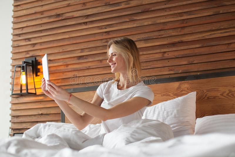 Uma mulher de sorriso encontra-se no desdobramento da cama através de sua tabuleta imagens de stock