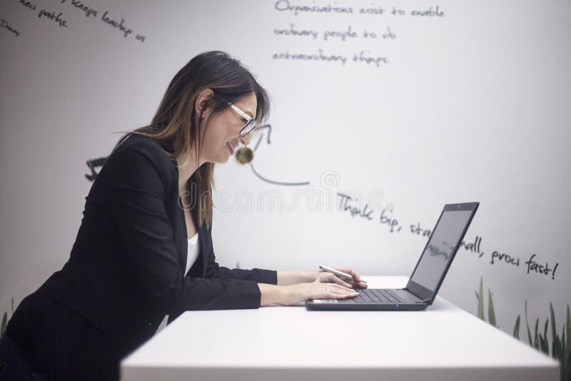 Uma mulher de sorriso nova, 30-39 anos velha, vista lateral, tiro da parte superior do corpo Trabalho no portátil parede com cita fotos de stock