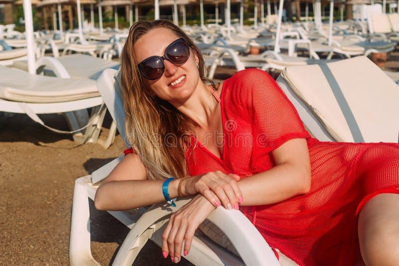Uma mulher de sorriso nova encontra-se em um vadio branco fotos de stock royalty free