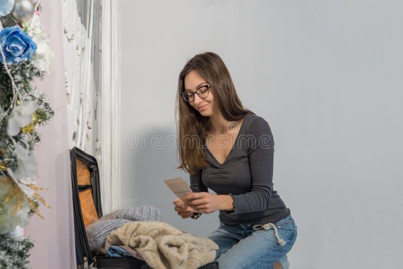 Uma mulher de sorriso nova está embalando uma mala de viagem para uma viagem a um país frio em Rússia Inverno A parte traseira po foto de stock