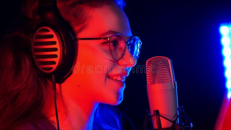 Uma mulher de sorriso nova nos vidros que canta pelo microfone na iluminação de néon no estúdio foto de stock royalty free