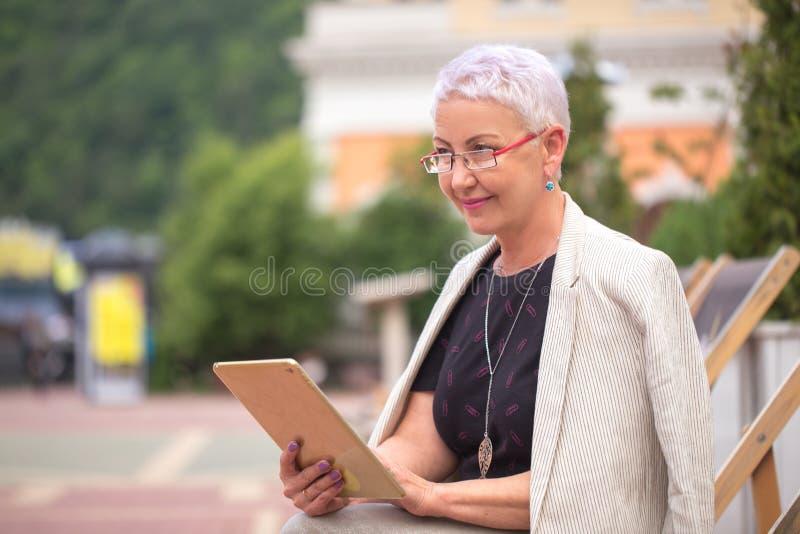Uma mulher de sorriso que pensa sobre seu negócio na rua imagens de stock royalty free