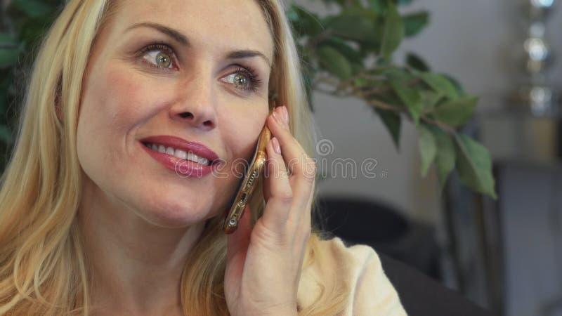 Uma mulher de sorriso tem uma conversa telefônica foto de stock