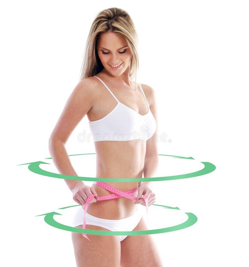 Uma mulher do ajuste mede seu corpo com uma fita foto de stock