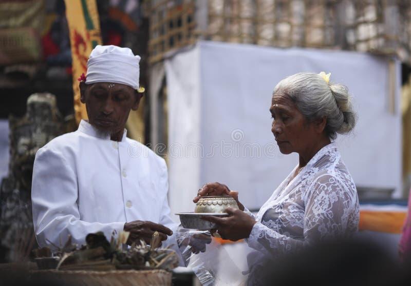 Uma mulher do Balinese e um padre local na roupa tradicional na cerimônia do templo hindu, ilha de Bali, Indonésia imagem de stock royalty free